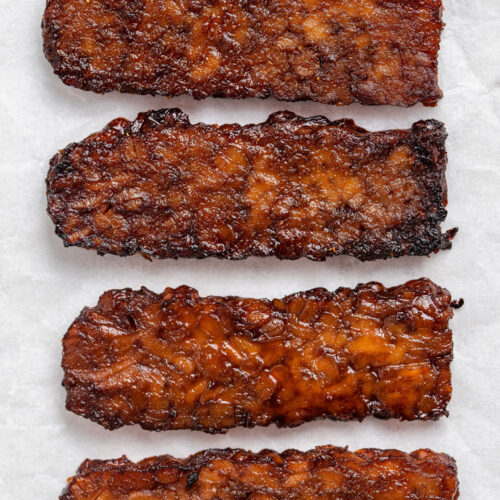 close up of four strips of cooked tempeh bacon