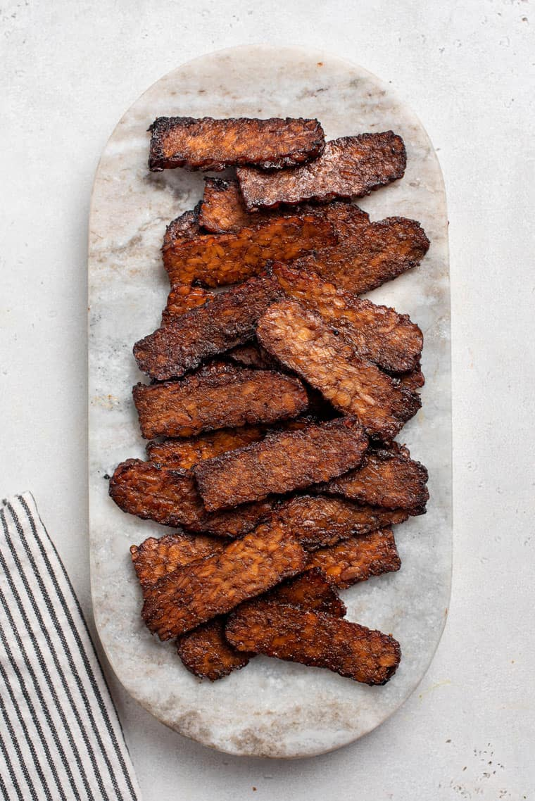 overhead of cooked tempeh bacon on marble board