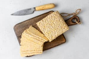 overhead of sliced tempeh on a wood cutting board