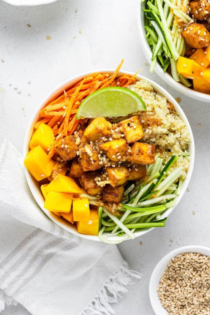 overhead of teriyaki quinoa bowls with mango, tofu and sesame dressing