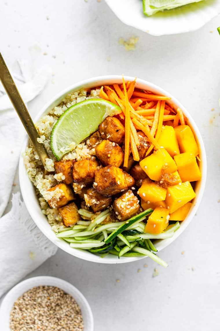 white bowl of teriyaki tofu, quinoa and mango