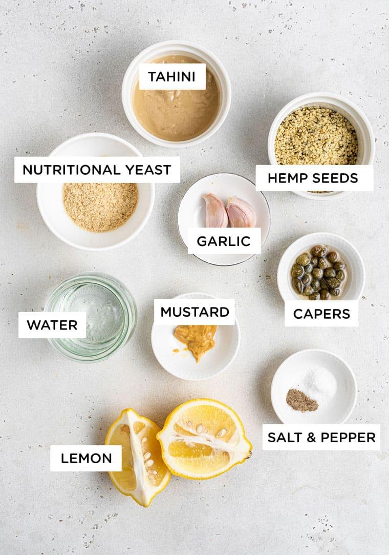 Ingredients for vegan caesar salad dressingwith nutritional yeast, garlic and tahini