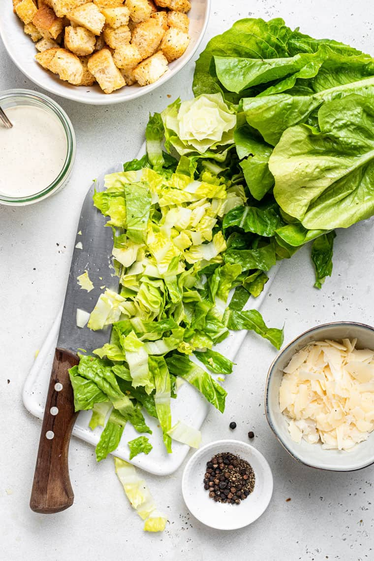 chopping romaine lettuce on a cutting board for salad