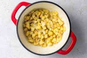 overhead of red pot with sauteed potatoes, onion and garlic for vegan corn chowder